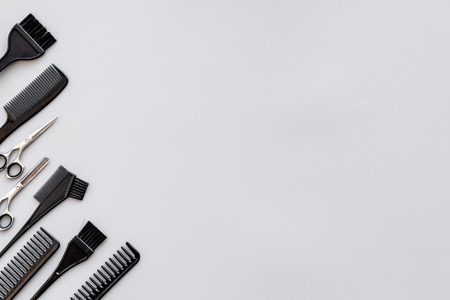 Beauty saloon equipment. Hairdress and haircut. Combs, sciccors, brushes on grey background top view. Archivio Fotografico