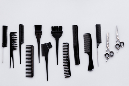 Hairdressing tools. Pattern with various combs and brushes on grey background top view. Stock Photo