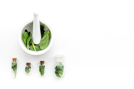 Herbal medicine. Herbs in mortar bowl and in small bottles on white background top view. Stock fotó