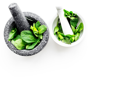 Herbal medicine. Herbs in mortar bowl on white background top view.
