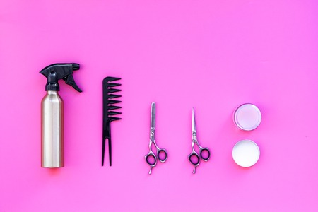 Professional tools for haircut. Sciccors, comb, spray on pink background top view copy space