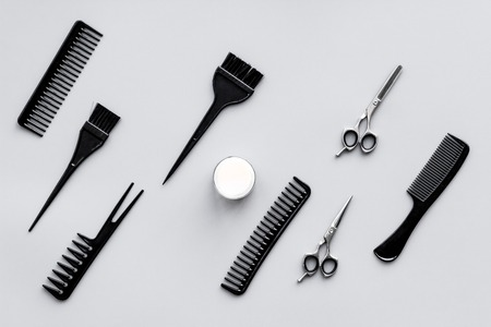 Beauty saloon equipment. Hairdress, haircut. Combs, sciccors, brushes on grey background top view