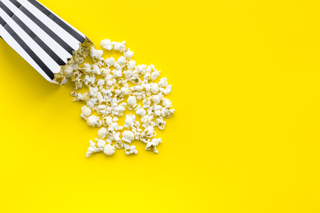 Popcorn in paper bag scattered on yellow background top view copy space