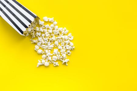 Il popcorn in sacco di carta ha sparso sullo spazio giallo della copia di vista superiore del fondo