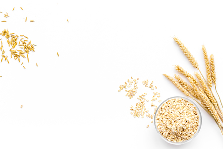 Cereals concept. Oatmeal in bowl near sprigs of wheat on white background top view copy space