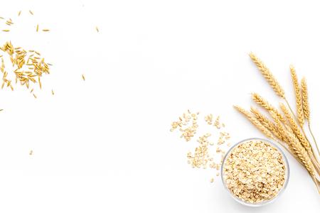 Getreide-Konzept. Hafermehl in der Schüssel nahe Zweigen des Weizens auf weißem Draufsicht-Kopienraum des Hintergrundes Standard-Bild