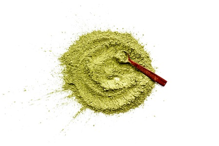 Powdered matcha green tea scattered on white background top view copy space