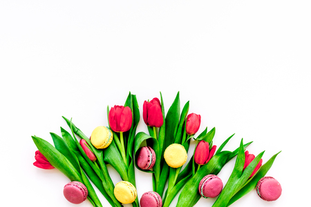 Spring gift. Flowers and sweets. Tulips and sweets macarons on white background top view.