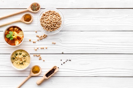 Cook chickpeas. Make hummus. Bowls with grains and ready meal near spices on white wooden background top view.