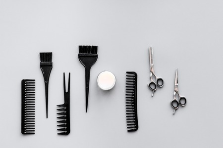 Beauty saloon equipment. Hairdress and haircut. Combs, sciccors, brushes on grey background top view. Stockfoto