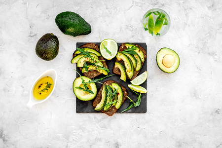 Have a bite with healthy snacks. Avocado toast on grey background top view. Banco de Imagens