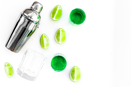 Make cocktail with absinthe. Shaker, shots, lime slices on white background top view,