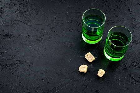 Absinthe shots near sugar cubes on black background top view.