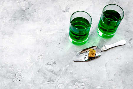 Traditions of drinking absinthe. Special spoon and sugar cubes near shots on grey background top view.