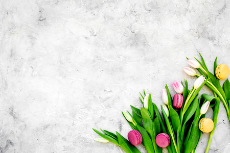 Spring bouquet of delicate pink tulips and sweets sweets macarons on grey background top view.