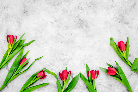 Bright red tulips for spring bouquet on grey background top view.