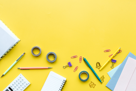 Scattered stationery on students desk. Yellow background top view.