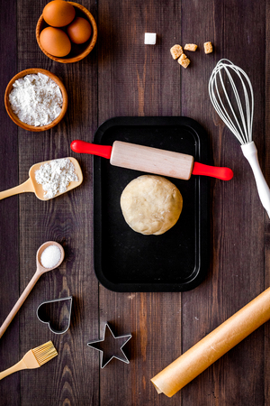 Ball of fresh raw dough near ingedients and cookware on dark wooden background top view. Foto de archivo