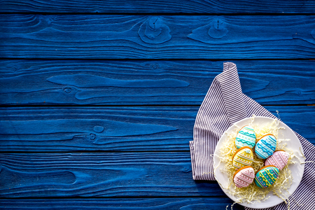 Easter eggs cookies. Sweets, pastry for Easter table. Blue wooden background top view.
