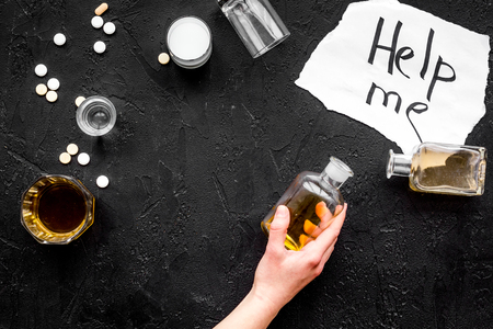 Treat alcohol dependence. Words Help me near glasses, bottles and pills on black background top view.