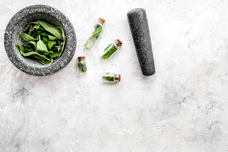 Phytotherapy. Herbs in mortar bowl and in small glasses on grey background top view.
