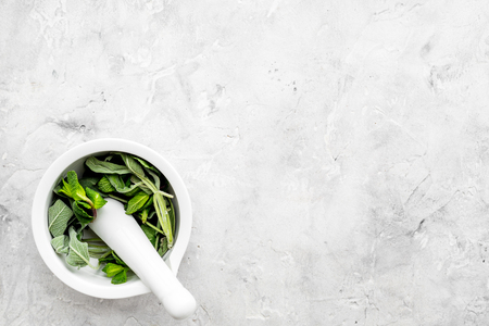 Phytotherapy. Herbs in mortar bowl on white background top view. Banco de Imagens - 95333435