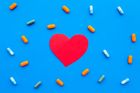 Vitamins of drugs for heart. Color pills near heart sign on blue background top view.
