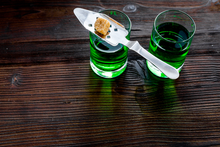 Traditions of drinking absinthe. Special spoon and sugar cubes near shots on dark wooden background top view.