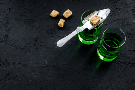 Traditions of drinking absinthe. Special spoon and sugar cubes near shots on black background top view.