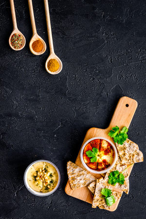 Hummus ready to eat. Bowl with dish among pieces of crispbread and spices on black background top view. Archivio Fotografico - 95354869
