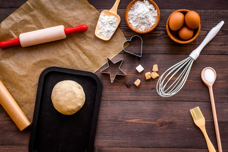 Roll out the dough. Dough ball near roller pin and other cookware on dark wooden background top view
