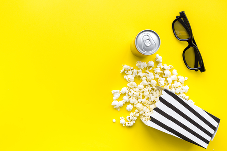 Cinema snacks. Popcorn in paper bag and soft drink near glasses on yellow background top view copy space Stock Photo