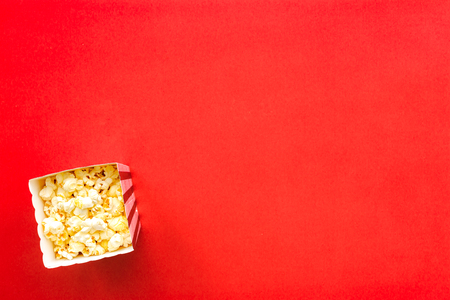 Popcorn in paper bag on red background top view copy space