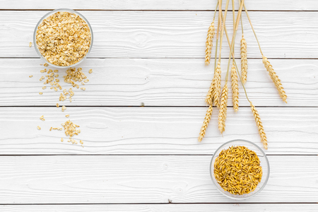 Food which rich with slow carbohydrates. Oatmeal and oat in bowls near sprigs of wheat on white wooden background top view copy space Stok Fotoğraf - 95374166