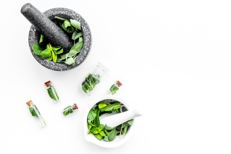 Phytotherapy. Herbs in mortar bowl on white background top view.