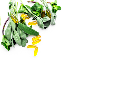 Alternative medicine. Phytotheraphy. Herbs and pills on white background top view.
