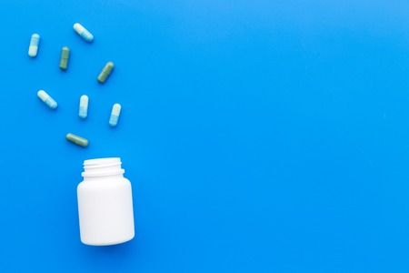 Medicine. Color capsules near pill bottle on blue background top view.