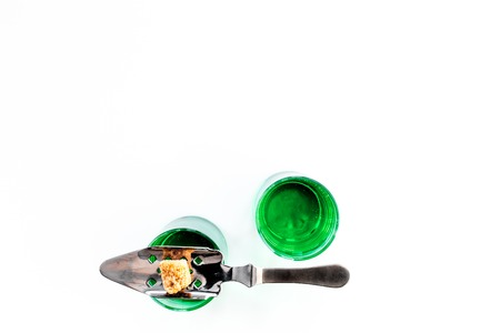 Traditions of drinking absinthe. Special spoon and sugar cubes near shots on white background top view.