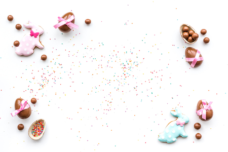 Celebrate Easter. Modern signs of Easter. Chocolate Easter eggs and Easter bunny cookies. White background top view.