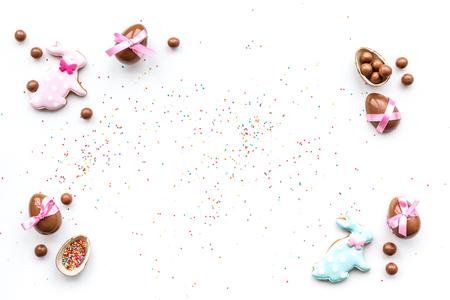 Feiern Sie Ostern. Moderne Zeichen von Ostern. Schokoladen-Ostereier und Osterhasenplätzchen. Draufsicht des weißen Hintergrundes. Standard-Bild - 95414083