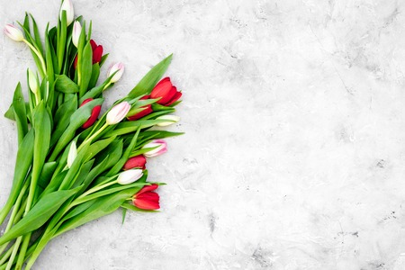 Spring bouquet of tulips on grey background top view.
