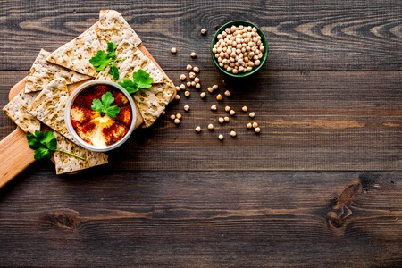 Serve hummus. Bowl with dish near pieces of crispbread on dark wooden background top view.