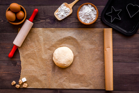 Roll out the dough. Dough ball near roller pin and other cookware on dark wooden background top view. Foto de archivo - 95414137
