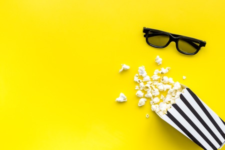 Watch film in cinema concept. Popcorn and glasses on yellow background top view.