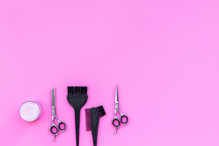 Professional hairdressing tools in beauty saloon. Sciccors, brushes on pink background top view copy space