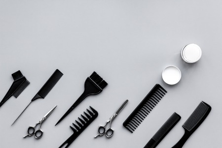 Beauty saloon equipment. Hairdress, haircut. Combs, sciccors, brushes on grey background top view copy space Stockfoto