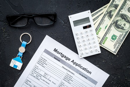 Housing loan. Draw up a mortgage. Mortgage application near keychain in shape of house and money on black background top view