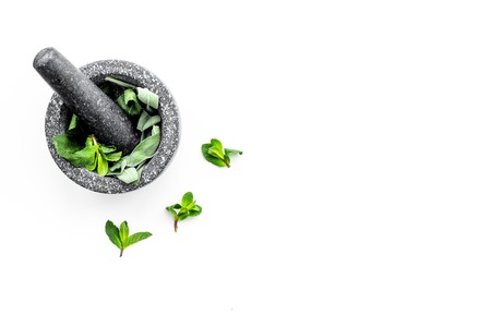 Phytotherapy. Herbs in mortar bowl on white background top view. Banco de Imagens - 95505753