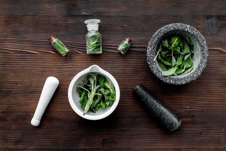 Harvest medicinal herbs. Greens in mortar bowl and herbs in small bottles on dark wooden background top view.