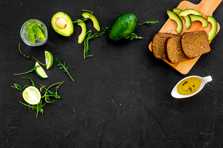 Breakfast for safety weight loss. Avocado toast with rye bread, lime, olive oil and greens on black background top view.